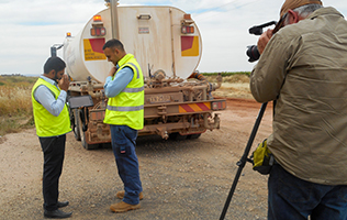 Two men in front of water truck being filmed while they are in discussion