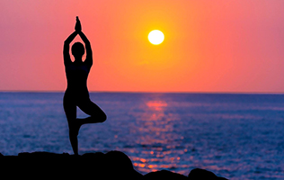 Woman doing yoga on cliff at sunset